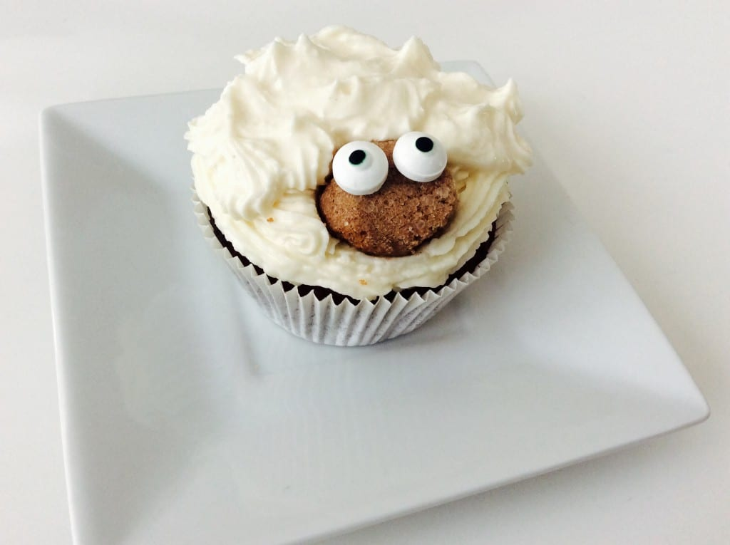 Die Creme mit dem Spritzbeutel auf dem ausgekühlten Muffin verteilen. Eine Biskotte mit einem groben Küchenmesser rundlich schnitzen und im unteren Drittel des Muffins platzieren. Dann die Augen mit kleinen Schokoklecksen fixieren.