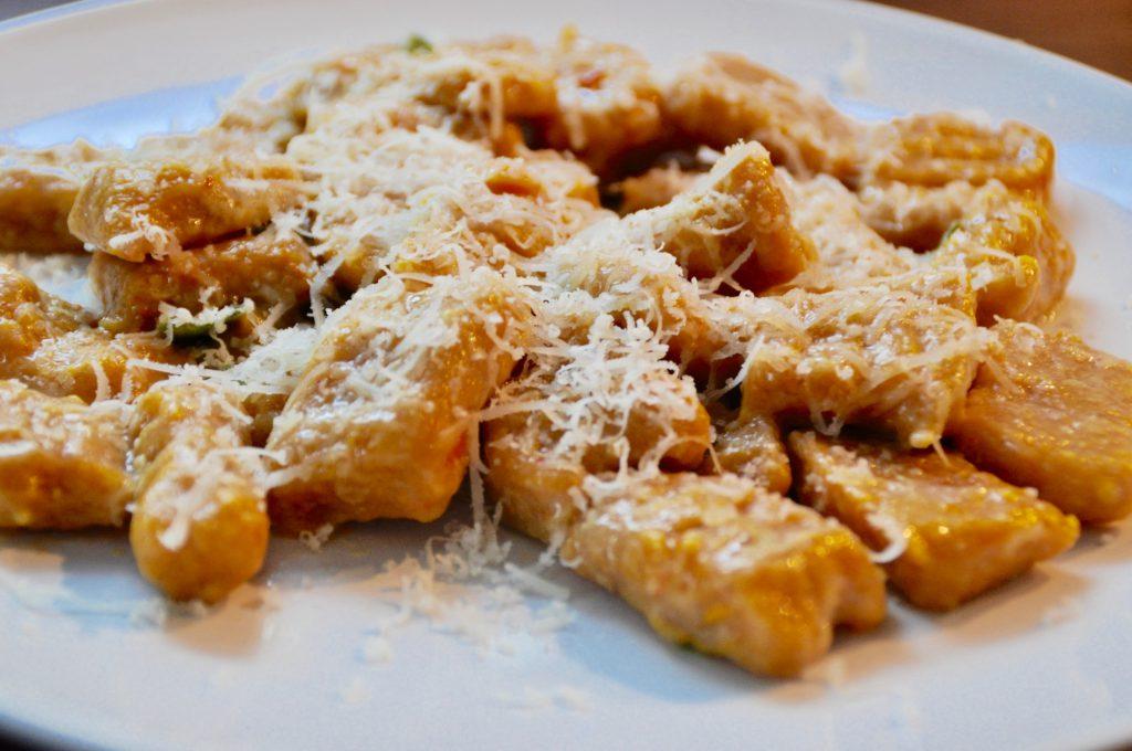 Kürbisgnocchi in Salbenbutter schwenken und mit frisch geriebenem Parmesan bestreuen